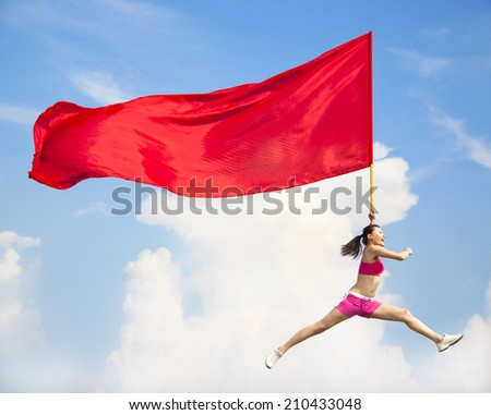Beautiful Asian female jumping with big red flag with blue sky