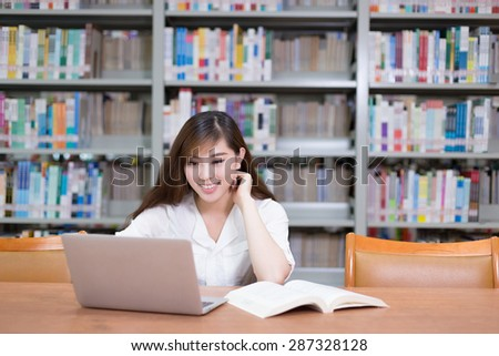 Beautiful asian female student using laptop for study in library with bookshelf background. - stock photo