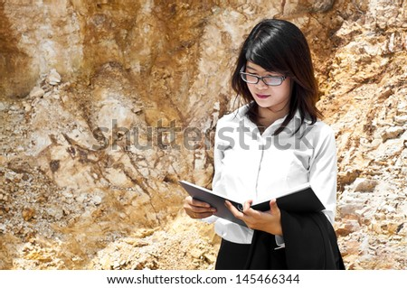 Beautiful Asian geologist researching in stratigraphy. - stock photo
