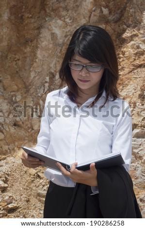 Beautiful Asian geologist woman reading report data. - stock photo