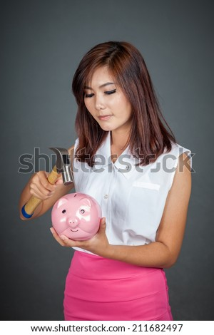 Beautiful Asian girl about to hit money box with hammer on gray background