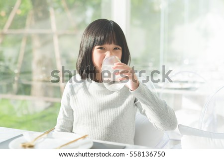 Beautiful Asian girl drinking  glass of water in a restaurant