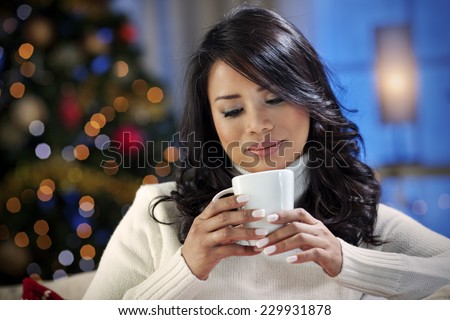 Beautiful asian girl drinking hot drink on a Christmas eve - stock photo