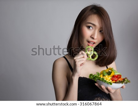 Beautiful asian girl eating healthy vegetables salad, looking away to copy space, healthy and diet concept.