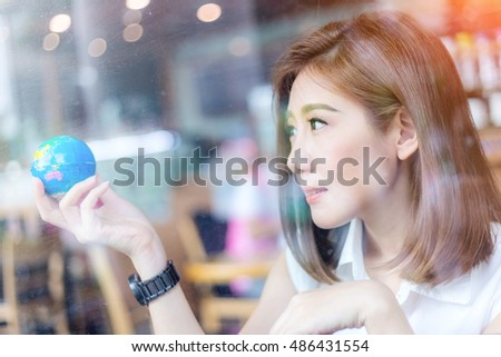 beautiful asian girl holding a globe  in her hand in cofffee shop with nature and light flare effect safe world concept