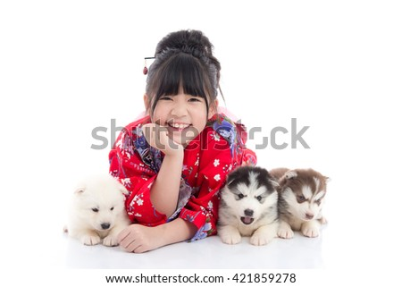Beautiful Asian girl  in red kimono lying with siberian husky puppies on white background isolated