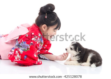 Beautiful Asian girl  in red kimono playing with siberian husky puppy on white background isolated - stock photo
