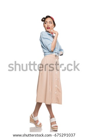 Beautiful asian girl in skirt and blouse posing and looking away isolated on white