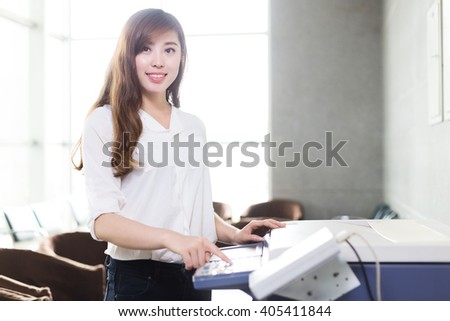 beautiful asian girl in white operating copier in modern office - stock photo