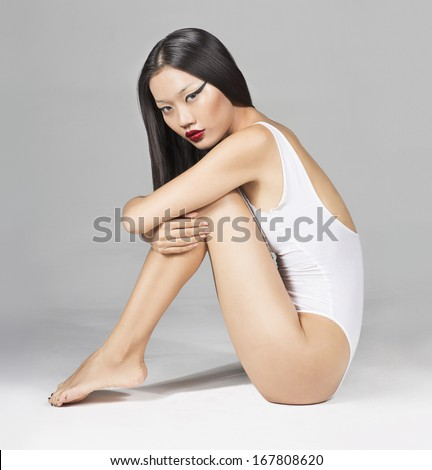 Beautiful Asian girl in white Swimsuit Sitting  - stock photo
