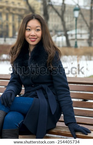 beautiful Asian girl in winter coat on the bench - stock photo