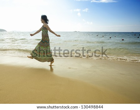 beautiful asian girl jumping on the beach against blue sky - stock photo