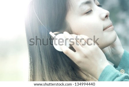 Beautiful asian girl listening music  in campus - stock photo