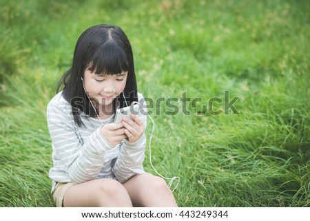Beautiful asian girl listening music in the park
