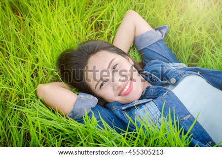 Beautiful asian girl lying on grass field and smiles