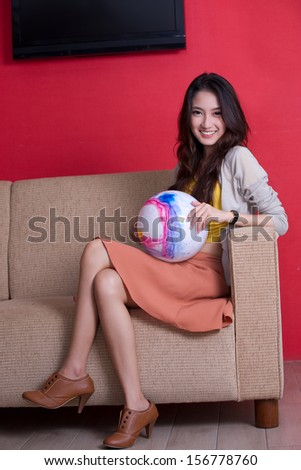 Beautiful asian girl on sofa with a ball