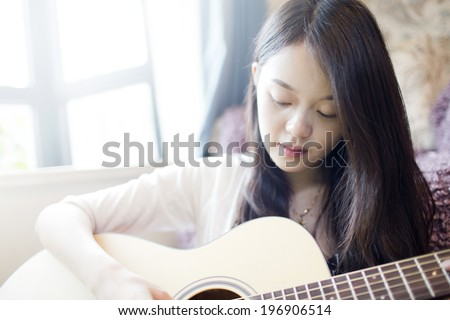 Beautiful asian girl playing guitar at home with smile - stock photo