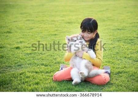 Beautiful asian girl playing with siberian husky puppy in the park - stock photo