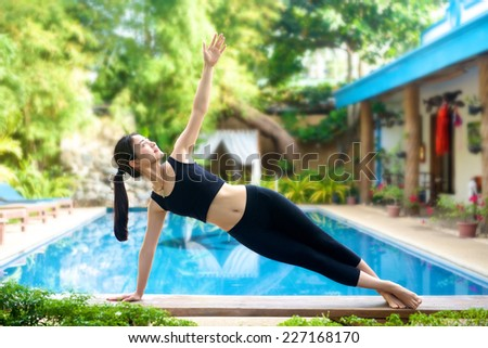 Beautiful Asian Girl practicing Vasisthasana yoga pose on a bench by the pool
