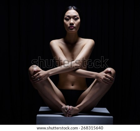 Beautiful Asian girl practicing yoga nude