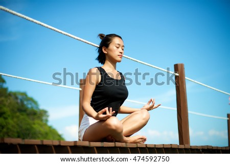 Beautiful Asian girl relax and meditate at the pier