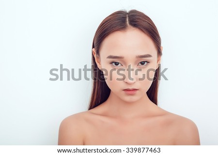 Beautiful Asian girl.She looks at the camera. Naked shoulders.