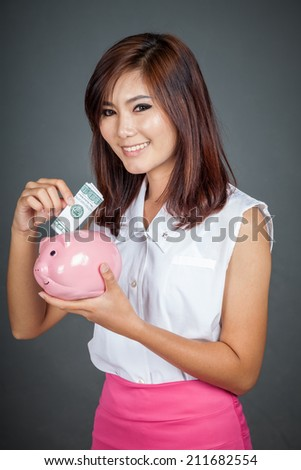 Beautiful Asian girl smile put a bill to pink pig money box on gray background