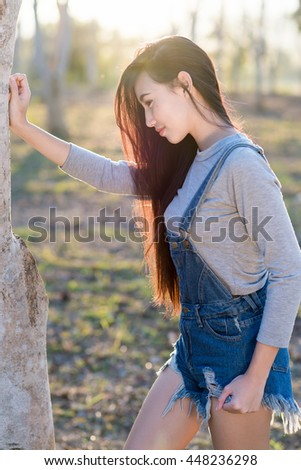 Beautiful asian girl standing in the park, sunshine flare.