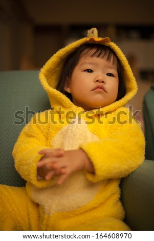 Beautiful Asian Girl Toddler in Yellow Duck Suit - stock photo