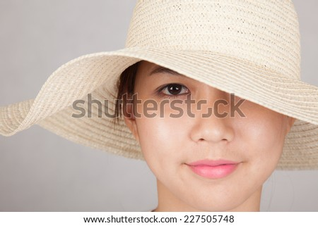 Beautiful Asian girl with sun hat on gray background
