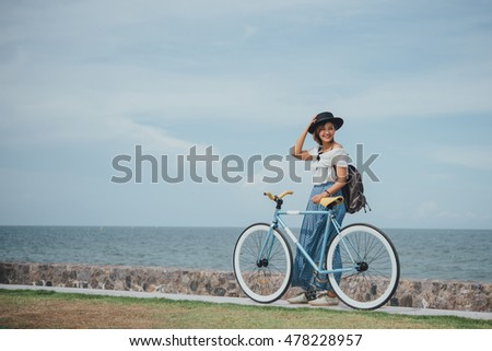 Beautiful Asian girl with vintage bicycle blue sea and blue sky background vintage color tone