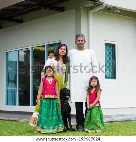 Beautiful Asian Indian family portrait smiling and standing outside their new house with pet dog.
