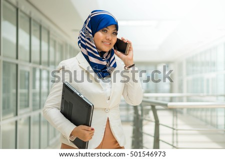 Beautiful Asian lady holding mobile phone and laptop outdoor