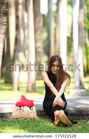 Beautiful Asian lady in black dress, posing in the park, greenery in the background, model is Thai Ethnicity.