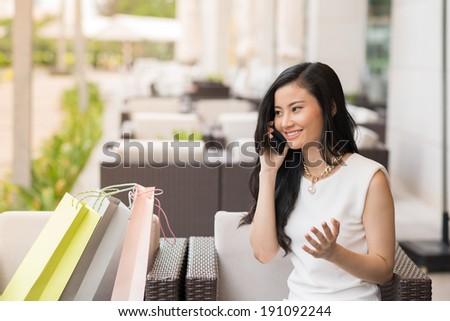 Beautiful Asian lady talking on the phone - stock photo