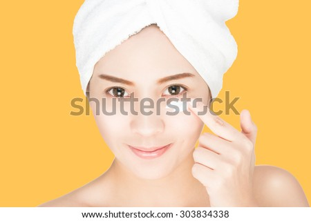 beautiful asian model applying  skin cream under eyes on her face, anti-aging skin care cream, isolated with clipping path  - stock photo