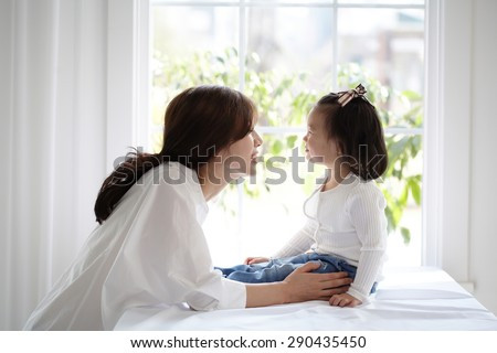beautiful Asian mom and her cute daughter kissing with love while looking at each other