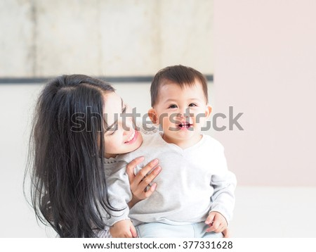 Beautiful Asian mother and son on pastel color background.
