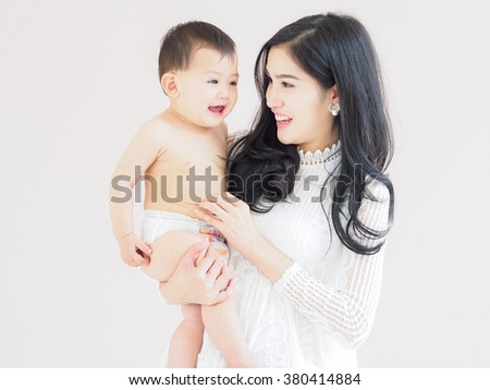 Beautiful Asian mother and son on pastel color background. - stock photo