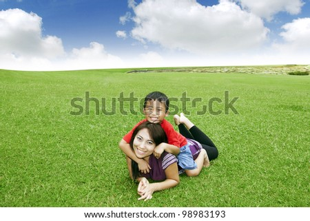 Beautiful Asian mother smiling with her cute son in meadow