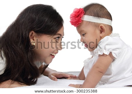 Beautiful Asian mother staring at her cute baby daughter on bed, isolated on white background - stock photo