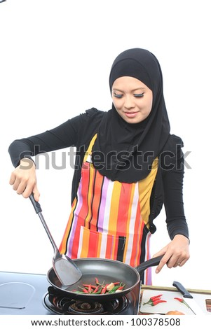 Beautiful asian muslim woman cooking and smile while looking to the camera in the kitchen isolated white background - stock photo