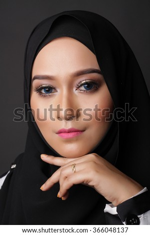 beautiful asian muslimah woman with natural face on dark gray background