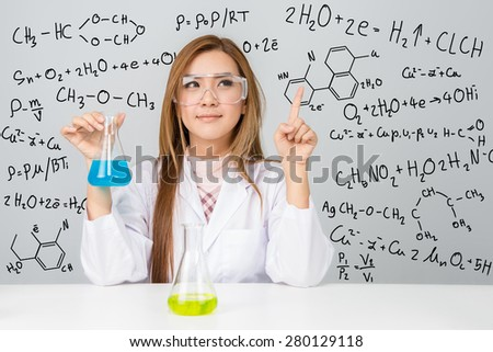 Beautiful Asian scientific researcher holding a liquid solution with science or chemistry formula