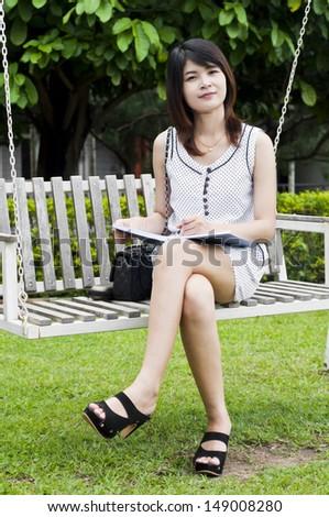 Beautiful Asian student woman on white wooden swing. - stock photo