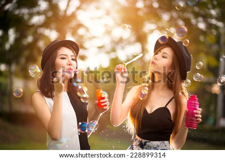 Beautiful asian teen girls blowing soap bubbles, Outdoor portrait - stock photo