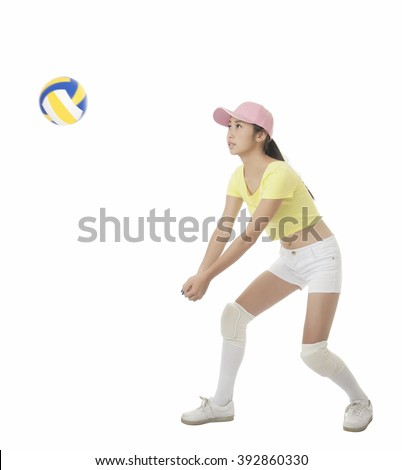 Beautiful Asian teenage girl hitting a volleyball isolated on white background