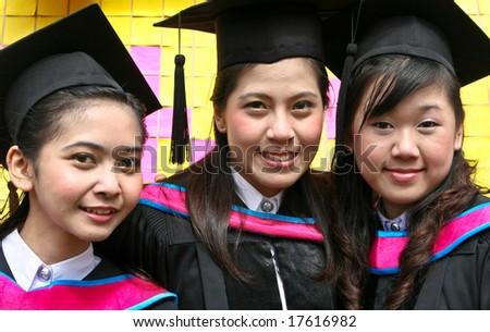 Beautiful Asian university graduates celebrate their success. - stock photo