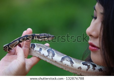 Beautiful Asian Woman and a snake in the garden of eden