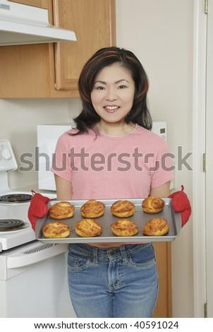 Beautiful Asian woman baking Cinnamon Rolls - stock photo